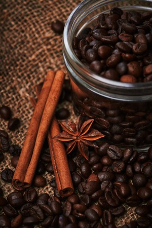 seed pots: Coffee beans in jar with cinnamon and star anise on sackcloth