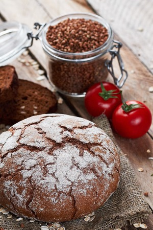 tommy: Closeup photo of rustic floured bread on sackcloth, two pieces of brown tommy, tomatoes, oat flakes and jar with buckwheat on planked wooden table