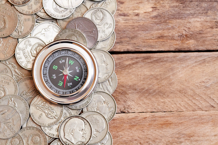 azimuth: Metal compass and old coins on the wooden table