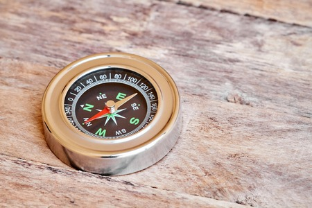 magnetic north: Travel background. Metal compass on the wooden table