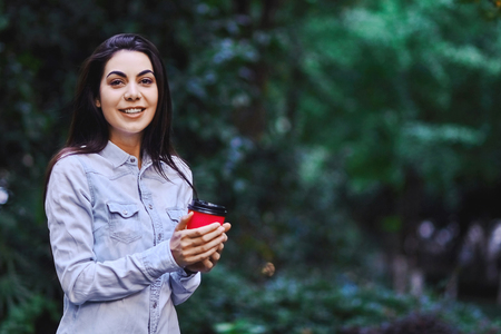Young smiling woman holding the cup of coffee