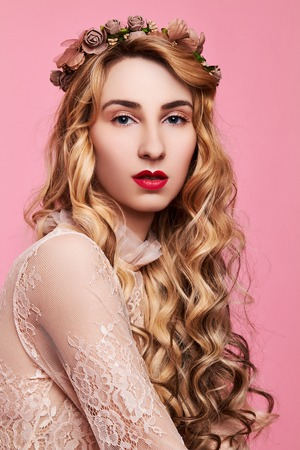 Fashion photo of young woman on pink background wearing gold diadem