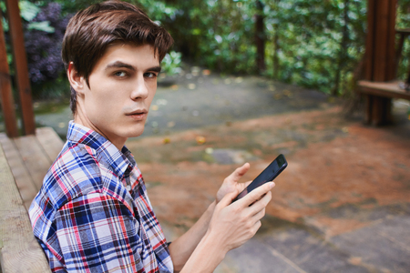 Man is sitting in the wooden pavilion and looking at the cellphone in the forest