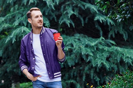 Man in the forest against green tree background with cup of coffee