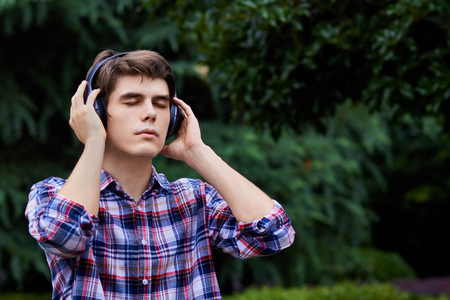Guy in the forest is listening to music Stock Photo