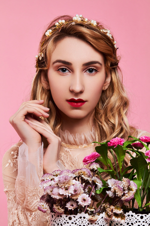 Fashion photo of young woman on pink background wearing gold diadem with flowers near her face Stock Photo