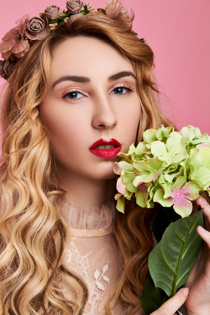 Fashion photo of young woman on pink background wearing flower wreath with flower near her face