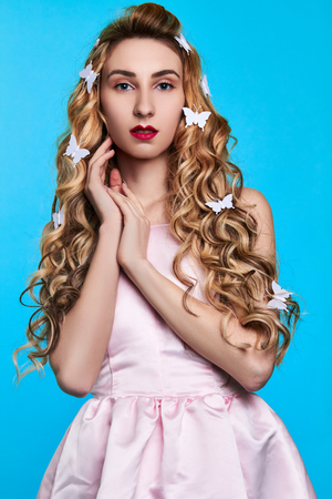 Fashion photo of young woman against blue background wearing pink dress and hair pins look like butterflies Stock Photo