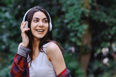 Young smiling woman listening to the music, through headphones on her head