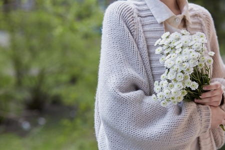 photo of young woman holding white flowers with green stem in her hands