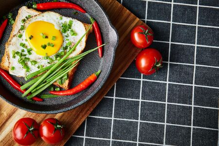 Scrambled eggs on the bread in the frying pan with vegetables