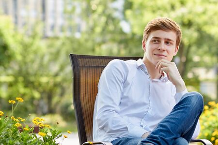 Young attractive man in white shirt sitting on brown chair in the park on green background