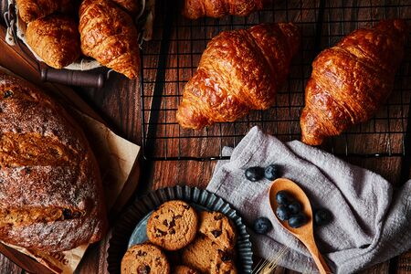 Delicious pastry and wheat spikes on the wooden table Фото со стока - 131839038
