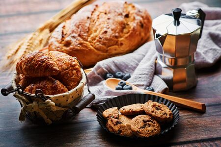 Miscellaneous delicious pastry and coffee pot on the wooden table