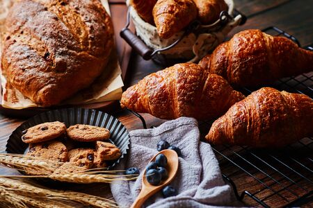 Delicious pastry and wheat spikes on the wooden table Фото со стока - 131838587