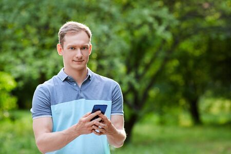 Photo of cellphone in mans hands on green blured background