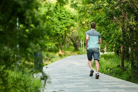 Man is jogging in the park on green background