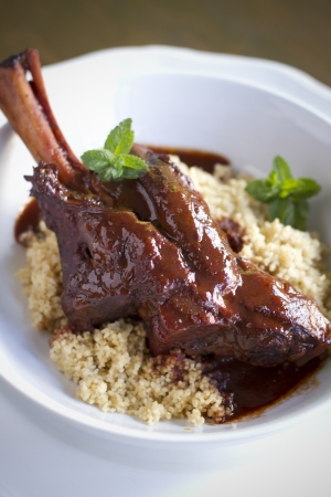 braised: Indian spiced, braised lamb shank over cous cous. Stock Photo