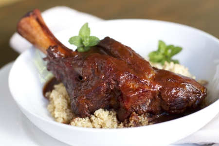 lamb shank: Indian spiced, braised lamb shank over cous cous. Stock Photo