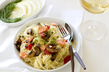 heaping: Salmon pasta with tomatoes, capers, and mushrooms. Stock Photo