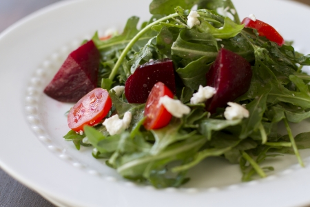 A fresh arugula salad with tomatoes and beets. Imagens
