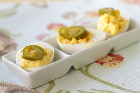 Spicy deviled eggs with jalepenos on top. Imagens
