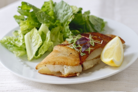 potato cod: Potato wrapped cod with a lemon wedge. Stock Photo