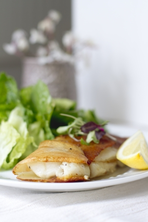 lemon wedge: Potato wrapped cod with a lemon wedge. Stock Photo