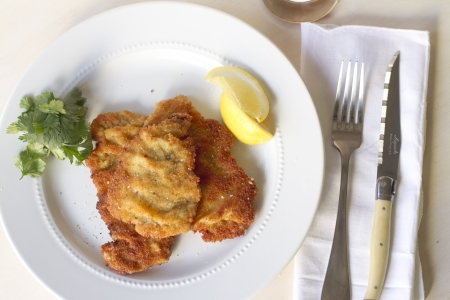 Veal weinerschnitzel on a plate with lemon and parsely garnishes.