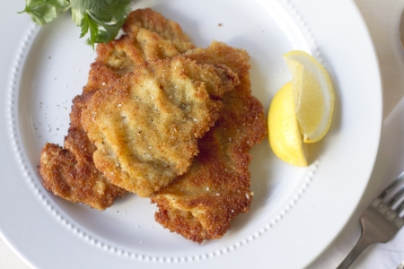 protien: Veal weinerschnitzel on a plate with lemon and parsely garnishes.