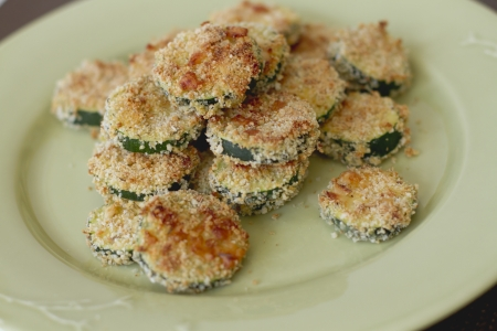 Breaded rounds of zucchini on a plate.