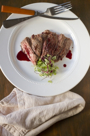 Cooked skirt steak with a pomegranate gastrique.