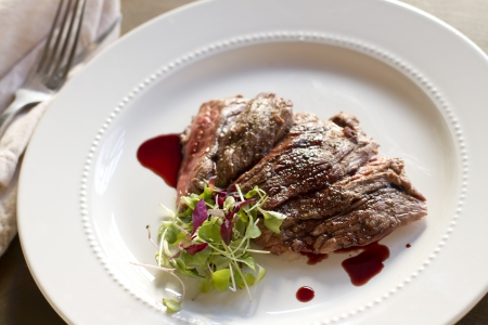 entree: Cooked skirt steak with a pomegranate gastrique.