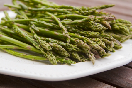 heaping: A heaping pile of green asparagus on a plate. Stock Photo