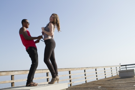 Two young people playing on a pier.