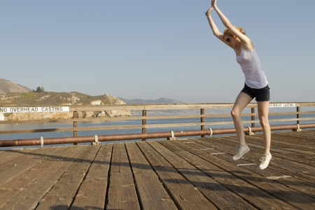 An attractive young woman does a cartwheel on a pier.