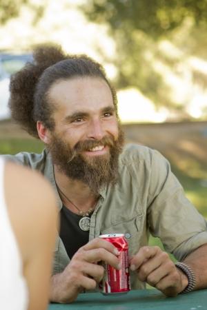 conversa: Un joven desali�ado bebe una bebida y habla con amigos.