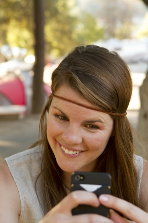 A young woman uses her phone while camping. Banco de Imagens