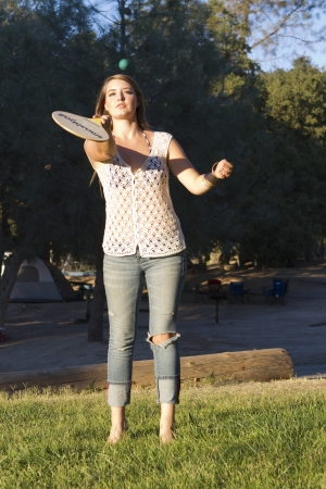 An attractive young woman plays paddle ball.