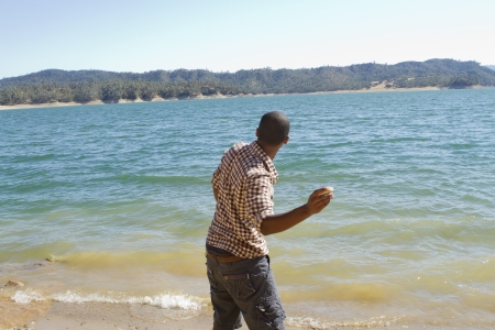 A young man skips stones into the water at the lake.
