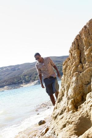 A young man walks alone along the shoreline of a lake