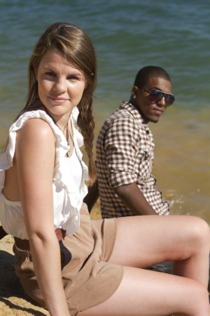neutrals: Two attractive people sitting by a lake  Stock Photo