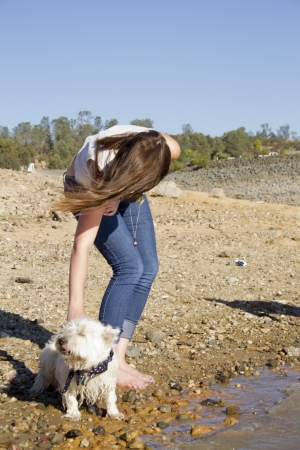 A young woman bends down to pet a Westie.