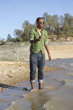 A hip young man plays in the water at the lake  Banco de Imagens