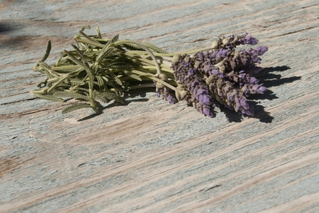 Several sprigs of lavender on a weathered table.