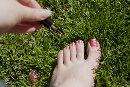 A woman paints her toenails in the grass.