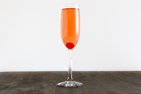 A cocktail of pink champagne with a cherry.