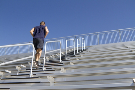 A Caucasian man in his twenties works out at a stadium. Stock Photo - 20887929