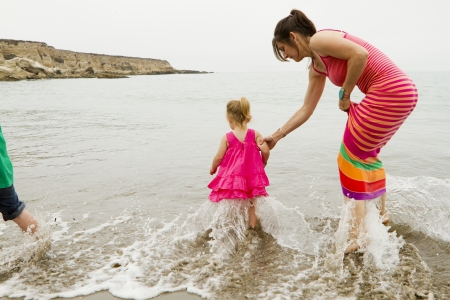 A mother with her daughter testing out the ocean.
