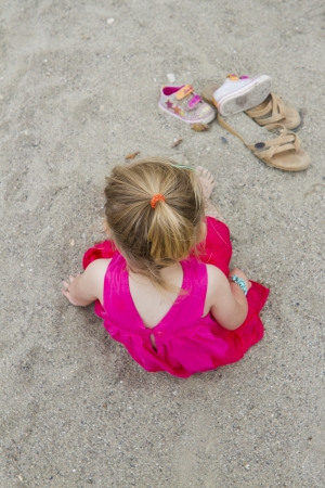 A toddler in a hot pink dress plays in the sand.
